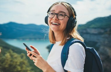 portrait smiling traveler blonde girl  with hipser glasses and backpack using smartphone device and listens music for headphones via Internet technology to enjoy hiking walk  on top of mountains, freedom holiday in nature