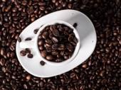 A csésze kávé kávébab kávébab háttér felett, felülnézet