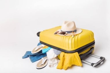 hat and sunglasses on a yellow suitcase with clothes of the traveler on a white background. Travel and adventure concept