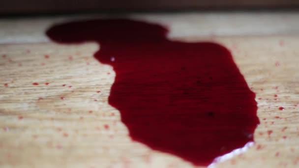vörös folyadék hasonló a vér csöpög a fa padló közelről. Vérkészlet a padlón.