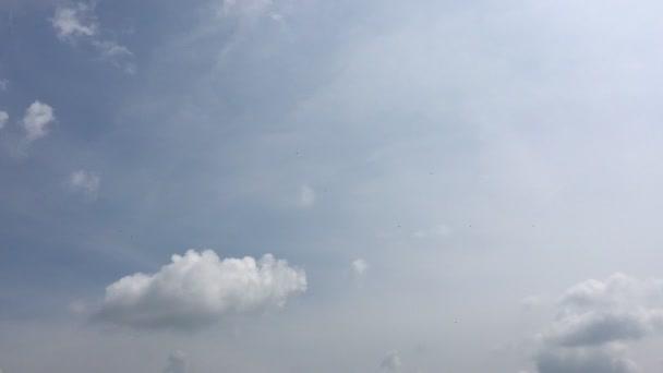 Fehér felhők eltűnik a forró nap a kék ég. Gyorsított mozgás felhő kék ég háttér. Kék ég, fehér felhők és a nap.