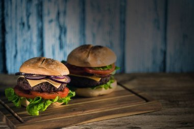 two fresh tasty cheeseburgers on wooden board, fast food concept