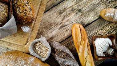 variety of delicious loaves of bread on wooden background