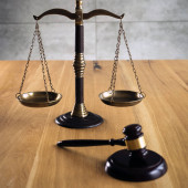 Law and Justice, judge gavel with scales on wooden table.
