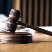 Recht und Gerechtigkeit, Richtergabel auf Holztisch mit verschwommenem Hintergrund.