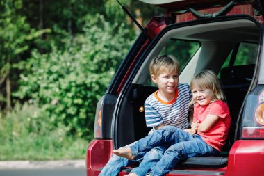 happy little girl and boy travel by car