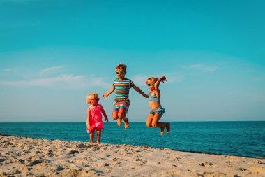 happy kids jump on beach, boy and girls having fun at sea