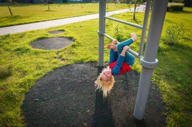 happy cute little girl upside down on monkey bars