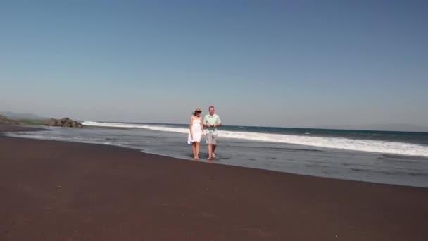 4k letecké létání video mladý pár na pláži s černým sopečným pískem při západu slunce. Ostrov Bali.