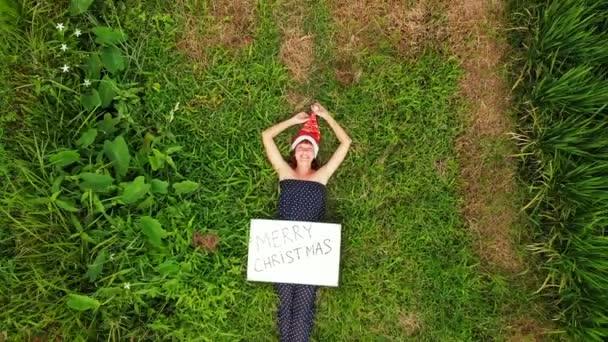 Mladá žena s červeným kloboukem a tabule s ručně psaný text Veselé Vánoce na tropické zelené pozadí. Vánoční pozdravy z ostrova Bali, Asie