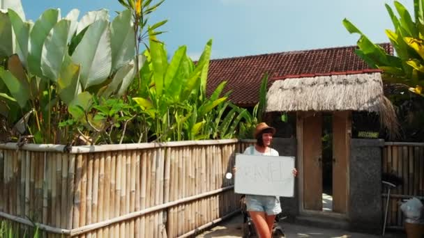 Young woman holding whiteboard with text travel. Travel concept, flying drone footage. Green background. Bali island.