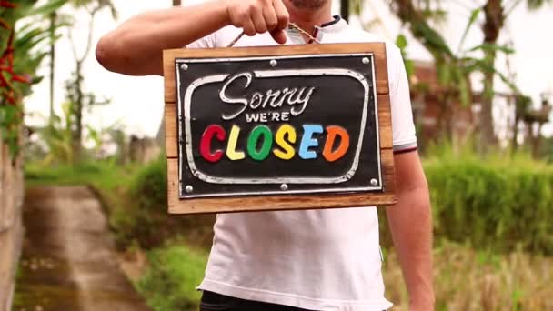 Man hands with closed sign board on a tropical nature background. Bali island.