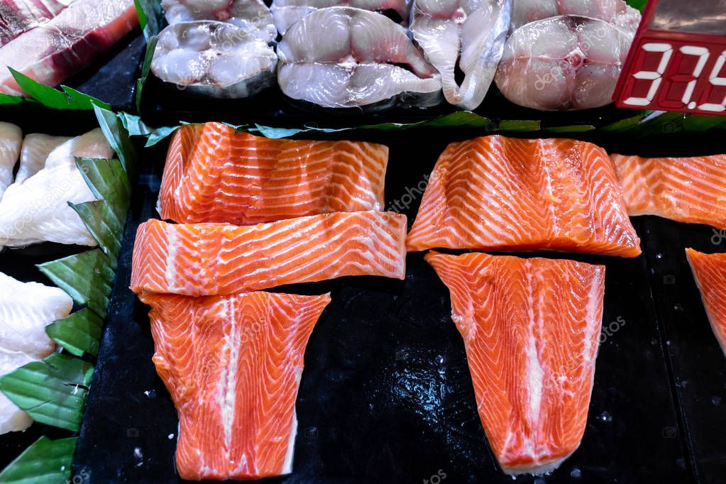 Fresh salmon fillet on sale in the seafood store. Fish fillet, frozen seafood.