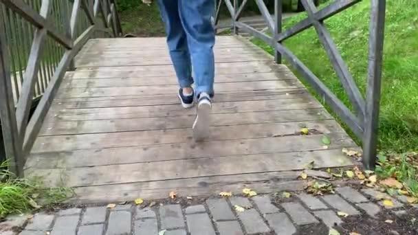 Weibliche Spaziergänge auf der Holzbrücke im Park.