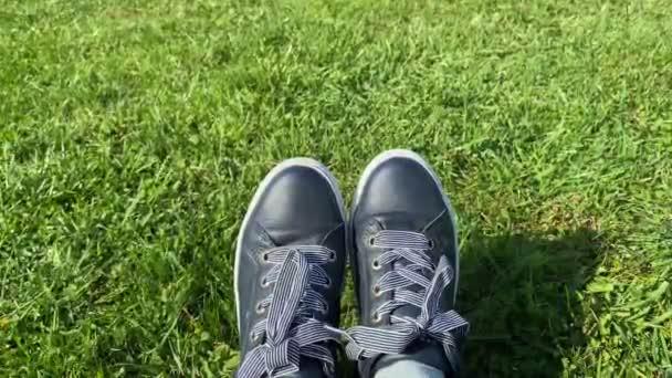 Weibliche Füße in Turnschuhen auf einem sonnenbeschienenen grünen Gras, Nahaufnahme.