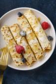 Fotografie Oben Sie Pfannkuchen mit Heidelbeeren und Himbeeren mit Karamell und Puderzucker auf dunkelblauem Hintergrund gerollt, Ansicht von