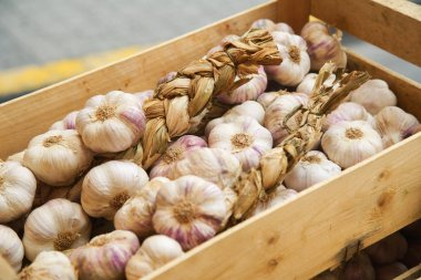 Garlic in wooden box on sale in french city market