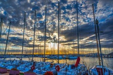 Cloudy sky over Alghero harbor at sunset. Sardinia, Italy