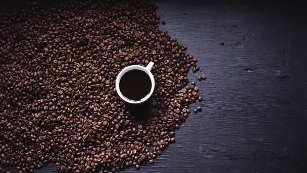 Černá káva v šálku a kávová zrna pozadí na tabuli