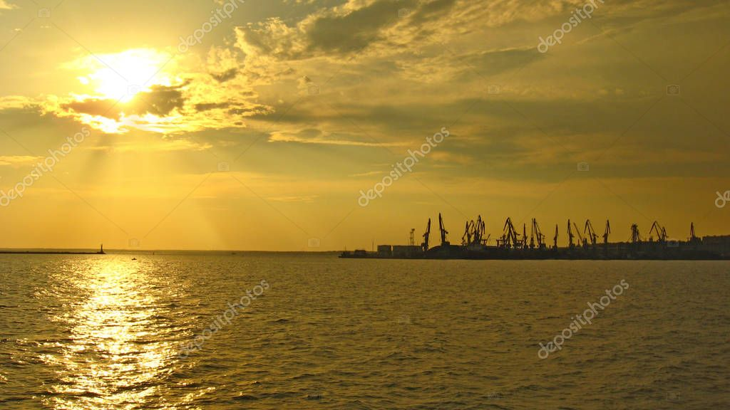 panorama of evening sea with docks and hoisting cranes. Evening marine landscape. Sunset above sea