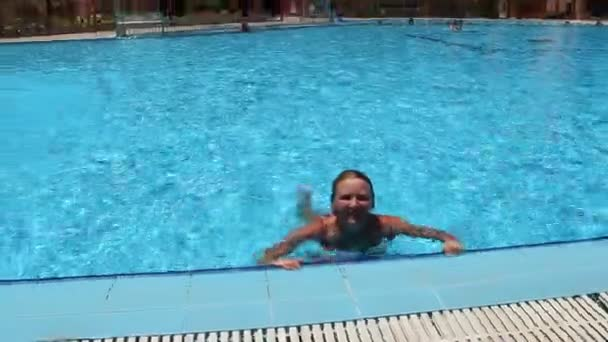 Attractive woman swimming in pool during vacation. Happy girl. Young woman enjoying summer vacations. Summer holiday in tropical resort
