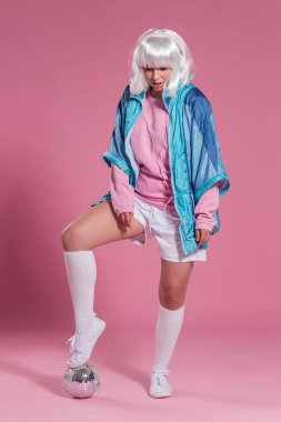 young woman with retro clothes listening to music and dancing against a pink background, studio shot