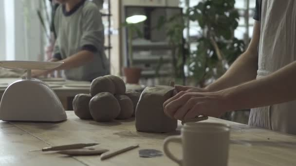 Two potters is doing job with clay in workshop.