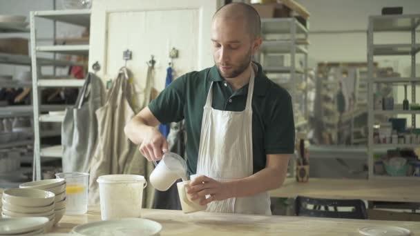 in der Werkstatt gießt Handwerker Flüssigkeit aus Tank in einen Becher mit Ton.