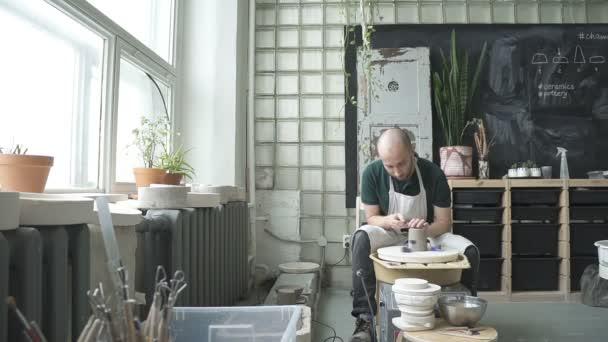 In der Töpferei schneidet Workshop Handwerker Form eine Ton-Schale mit einem Werkzeug.