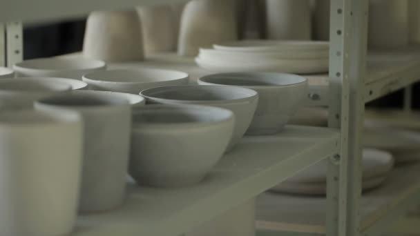 Close up of bowls and mugs on the shelf in ceramic studio.