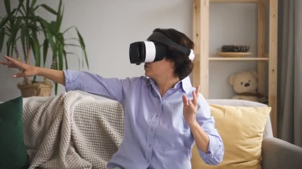 Mature woman is talking, testing virtual reality glasses in apartment interior.