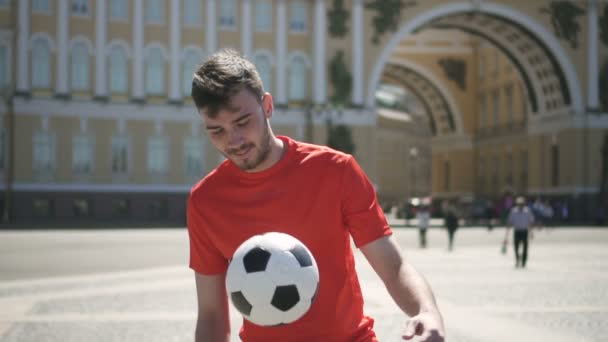 Handsome male football player kicking ball by his leg, taking in by the hand