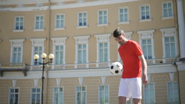 Handsome male football player kicking ball alone by his feet and breast on beautiful city square