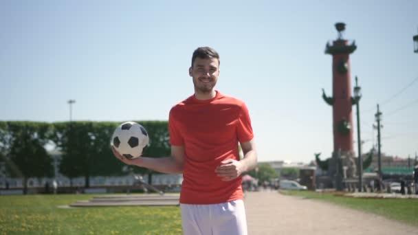 Mladý muž fotbalista, stojící, uvedení míč z ruky do ruky a usmívající se pěkný park