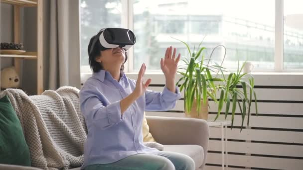 Elderly woman is using virtual reality glasses, sitting in home interior.