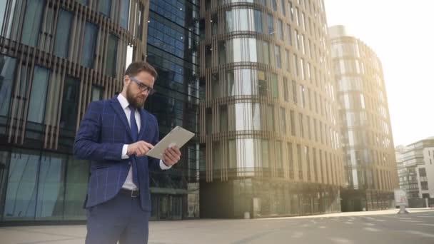 Pohledný podnikatel drží tablet stojící na ulici v letním dni