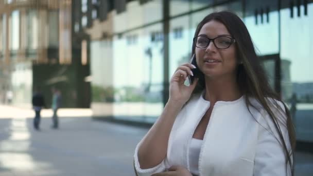 Beautiful businesswoman talking on phone standing near office building on street.