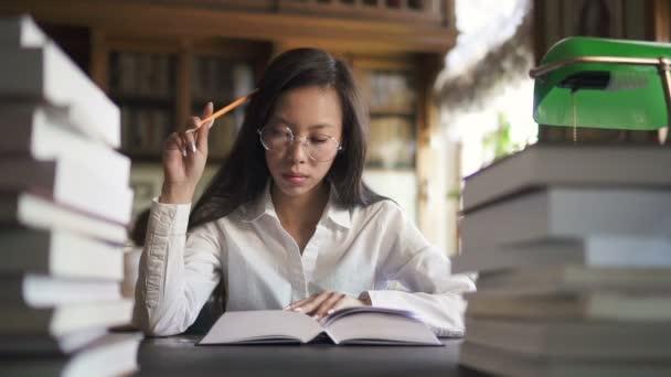 Krásná žena student je čtení knihy sedí u stolu v knihovně školy