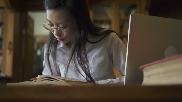 Krásná studentka studuje téma, sedí u stolu s knihami a přenosný počítač v knihovně