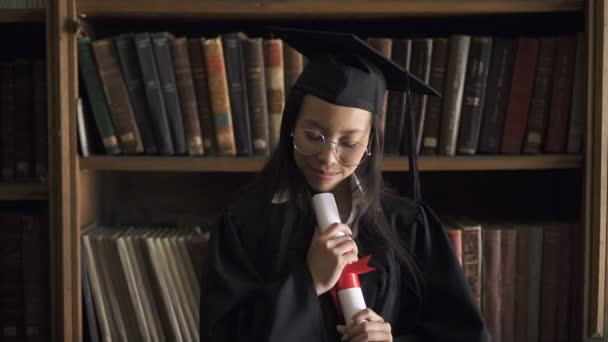 Happy asian student in round glasses and black gown enjoying