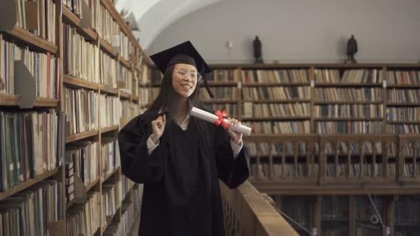 Atraktivní studentka v akademické šaty je baví, stojící v knihovně