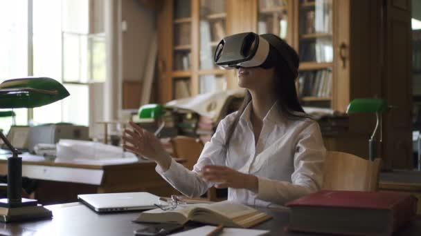 Young woman with virtual reality glasses on face, sitting in library, beautiful brunette is exploring fantastic 3d world using modern device at table in reading room of university. Concept: futuristic