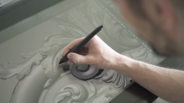 Restaurator arbeitet an Projekt mit Grafik-Tablet in modernem Atelier.
