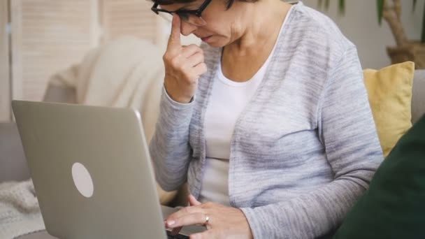 Mature woman in glasses working remotely on her computer