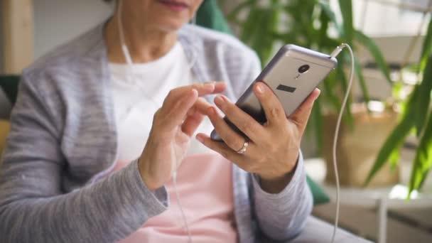 Reife Frau hält Smartphone in der Hand, hört Musik
