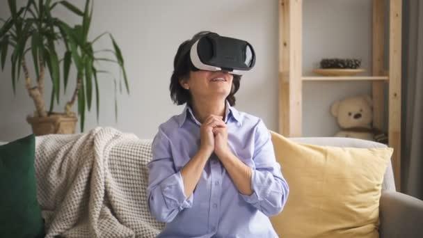 Žena v virtuální zřejmý brýle sedí na pohovce