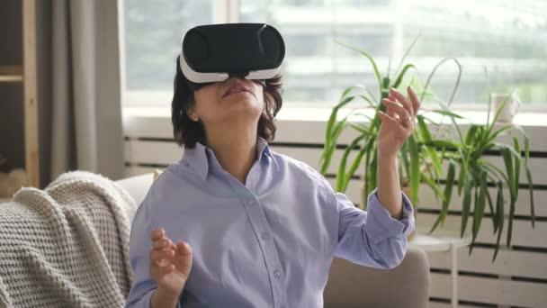 Mature woman testing virtual reality glasses