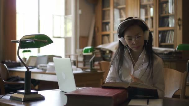 Mladá studentka právník je čtení knihy, psaní na notebooku posezení v knihovně