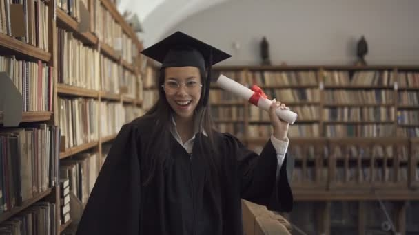 Female asian student lawyer in roung glasses and black gown holding
