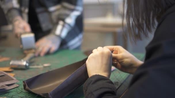 Mãos de detalhe de couro costura mestre feminino na oficina do couro–  gráficos de vetor a34e4852391
